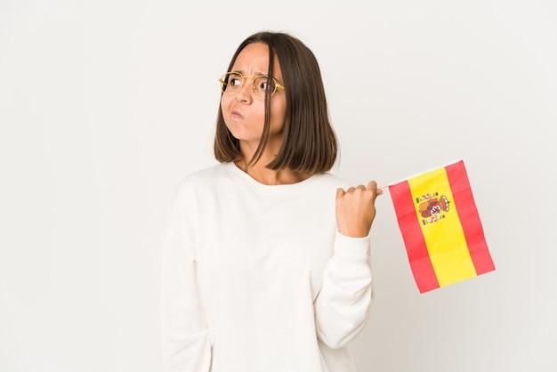 Młoda latynoska kobieta rasy mieszanej z hiszpańską flagą jest zdezorientowana, niepewna i niepewna.