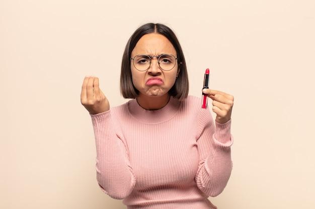 Młoda latynoska kobieta robi gest capice lub pieniądze, trzymając szminkę