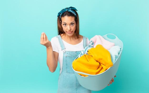 Młoda latynoska kobieta robi gest kaprysu lub pieniędzy, każąc ci zapłacić i prać ubrania