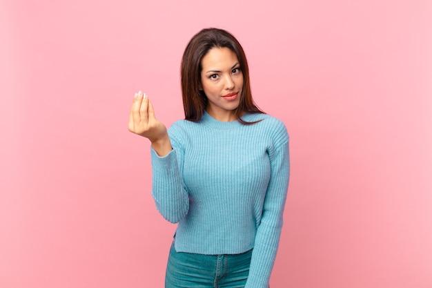Młoda latynoska kobieta robi gest kaprysu lub pieniędzy, każąc ci zapłacić