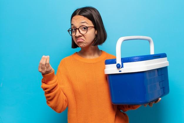 Młoda latynoska kobieta robi gest kaprysu lub pieniędzy