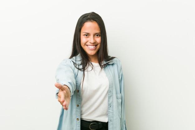 Młoda latynoska kobieta rozciąga rękę przy kamerą w powitanie gescie.