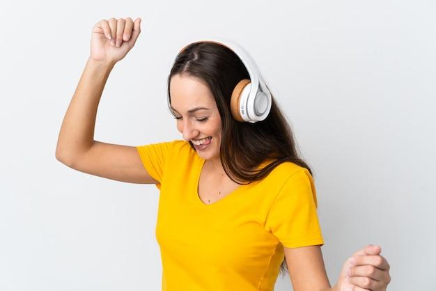 Młoda latynoska kobieta słucha muzyki i tańca na odosobnionym białym tle