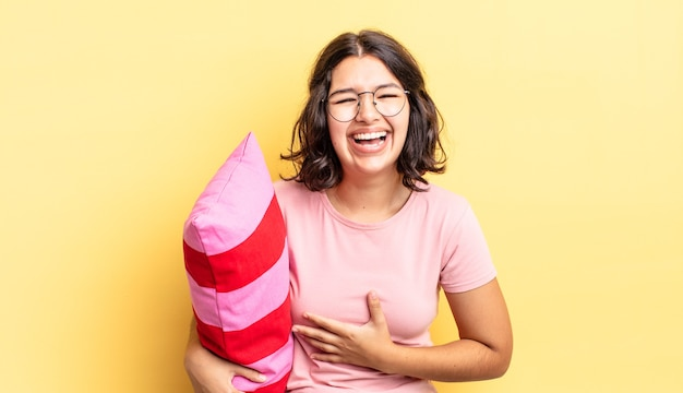 Młoda latynoska kobieta śmiejąca się głośno z jakiegoś przezabawnego żartu. koncepcja porannego budzenia