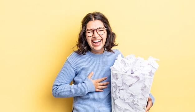 Młoda latynoska kobieta śmiejąca się głośno z jakiegoś przezabawnego żartu, nieudanego pomysłu na śmieci