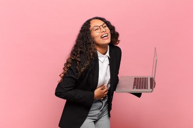 Młoda latynoska kobieta śmiejąca się głośno z jakiegoś przezabawnego żartu, szczęśliwa i wesoła, dobrze się bawi. koncepcja laptopa