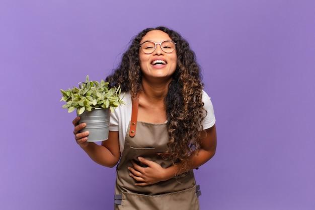 Młoda latynoska kobieta śmiejąca się głośno z jakiegoś przezabawnego żartu, szczęśliwa i wesoła, dobrze się bawi. koncepcja opiekuna ogrodu