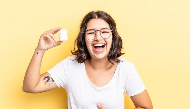 Młoda latynoska kobieta śmiejąca się głośno z jakiegoś zabawnego żartu. koncepcja pigułek na chorobę