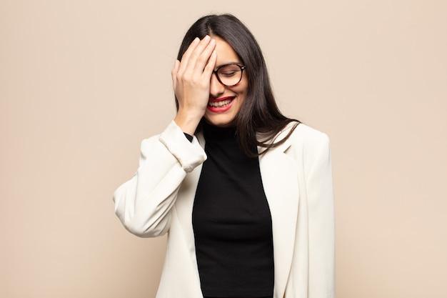 Młoda latynoska kobieta śmiejąca się i uderzająca w czoło