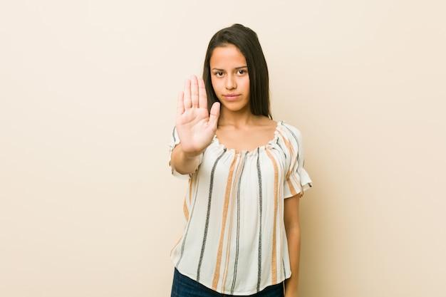 Młoda latynoska kobieta stoi z wyciągniętą ręką pokazując znak stop, zapobiegając ci.