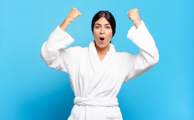 Młoda latynoska kobieta świętująca niewiarygodny sukces jak zwycięzca