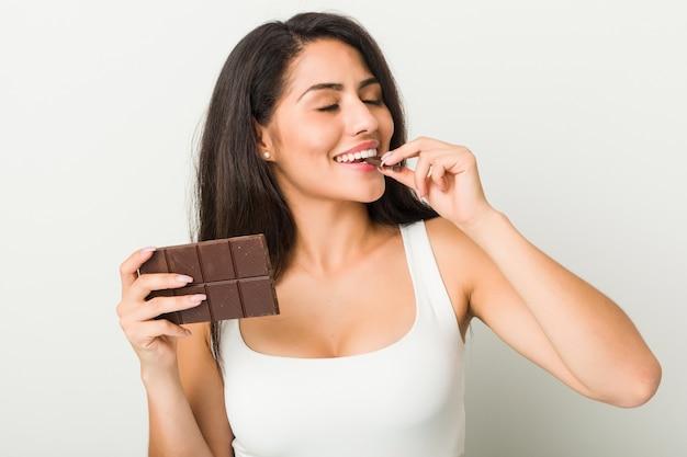 Młoda latynoska kobieta trzyma czekoladową pastylkę