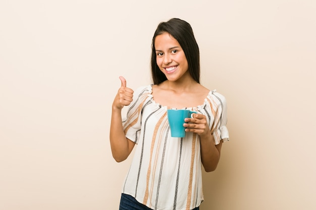Młoda latynoska kobieta trzyma filiżankę uśmiecha się kciuk up i podnosi