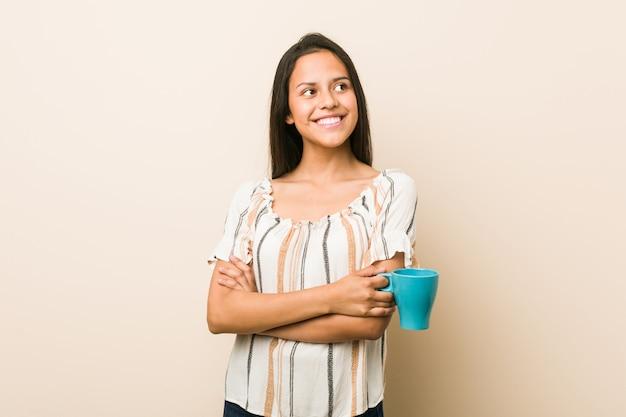 Młoda latynoska kobieta trzyma filiżanki ono uśmiecha się ufny z krzyżować rękami.