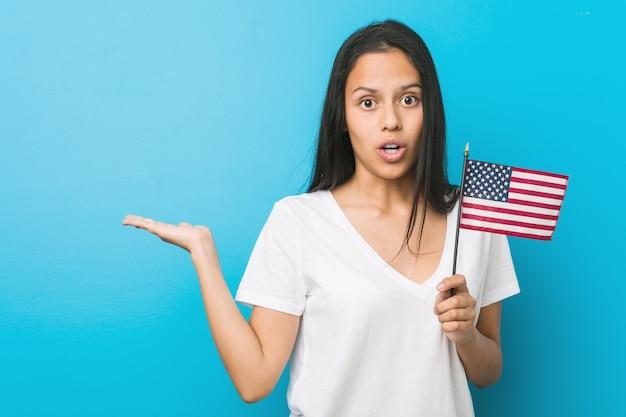 Młoda latynoska kobieta trzyma flaga stanów zjednoczonych pod wrażeniem trzyma kopii przestrzeń na palmie.