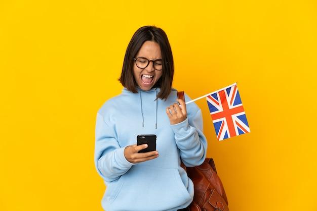 Młoda latynoska kobieta trzyma flagę wielkiej brytanii na białym tle na żółtym tle z telefonem w pozycji zwycięstwa