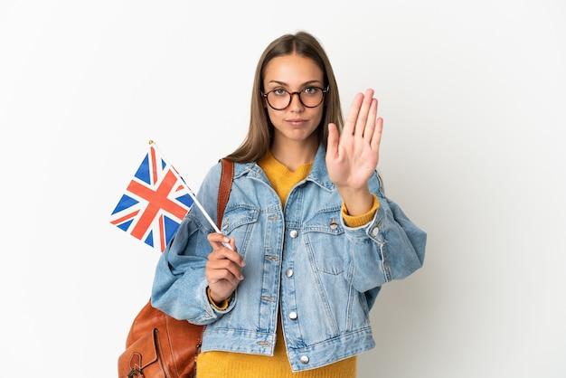 Młoda latynoska kobieta trzyma flagę wielkiej brytanii na białym tle, wykonując gest zatrzymania