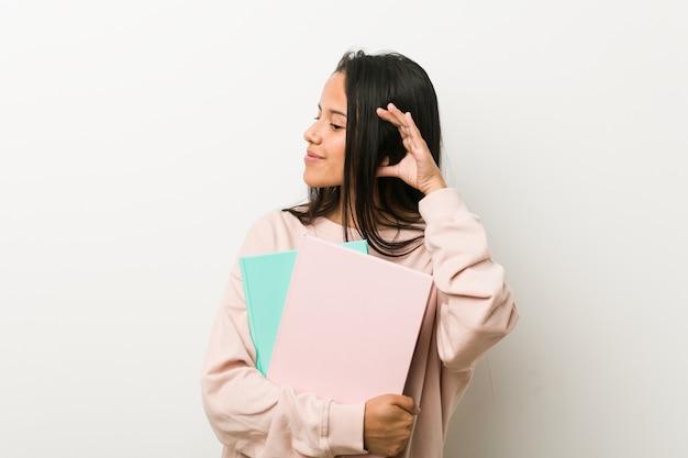 Młoda latynoska kobieta trzyma niektóre notatniki próbuje słuchać plotki.