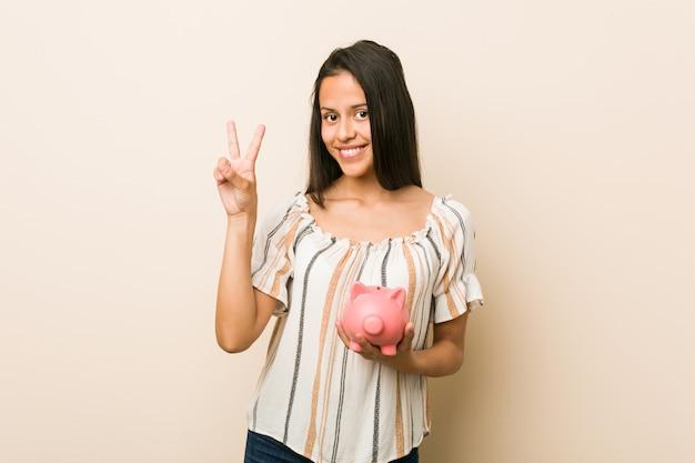 Młoda latynoska kobieta trzyma prosiątko banka pokazuje numer dwa z palcami.