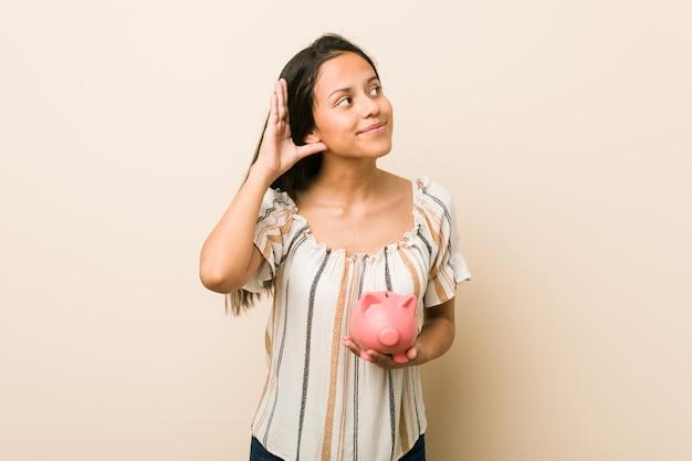 Młoda latynoska kobieta trzyma prosiątko banka próbuje słuchać plotki.