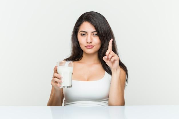 Młoda latynoska kobieta trzyma szklankę mleka pokazuje liczbę jeden z palcem.