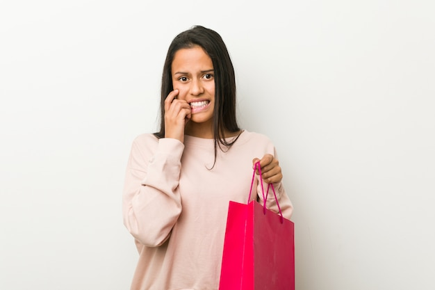 Młoda latynoska kobieta trzyma torbę na zakupy obgryzającą paznokcie, nerwowa i bardzo niespokojna.
