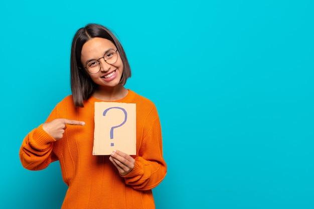 Młoda latynoska kobieta trzyma znak zapytania