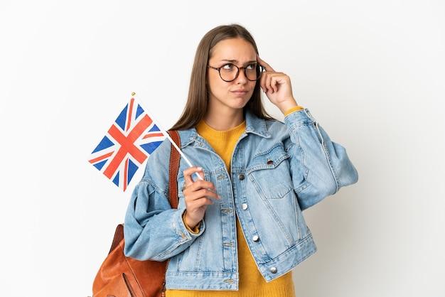 Młoda latynoska kobieta trzymająca flagę wielkiej brytanii na białym tle, mająca wątpliwości i myśląca