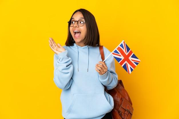Młoda latynoska kobieta trzymająca flagę wielkiej brytanii na białym tle na żółtym tle z niespodzianką wyrazem twarzy