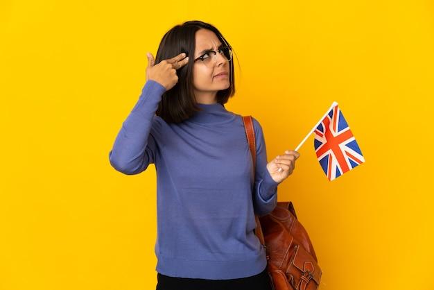 Młoda latynoska kobieta trzymająca flagę wielkiej brytanii na białym tle na żółtym tle z problemami z wykonaniem gestu samobójczego