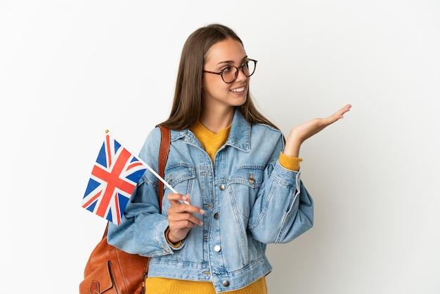 Młoda latynoska kobieta trzymająca flagę wielkiej brytanii nad białym tłem wyciąga ręce do boku, by zaprosić nas do odwiedzenia.