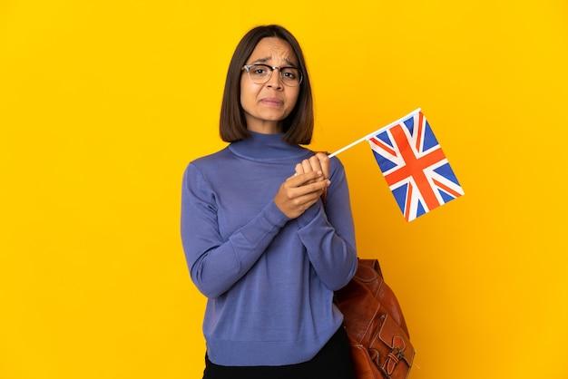 Młoda latynoska kobieta trzymająca flagę wielkiej brytanii odizolowana na żółtym tle śmiejąc się