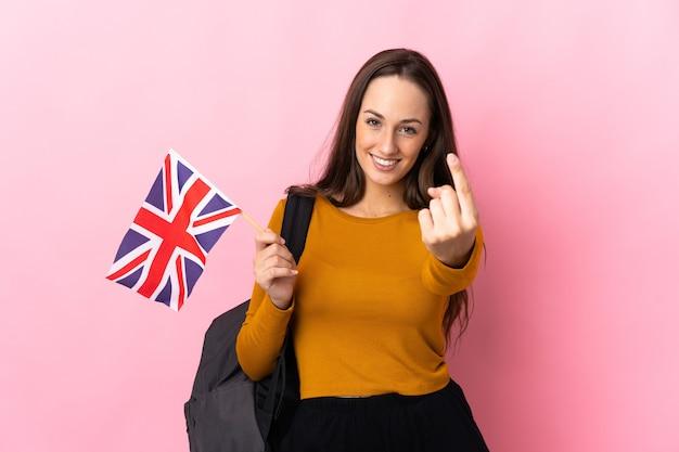 Młoda latynoska kobieta trzymająca flagę wielkiej brytanii robi nadchodzący gest
