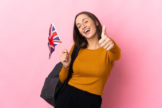 Młoda latynoska kobieta trzymająca flagę wielkiej brytanii z kciukami do góry, ponieważ wydarzyło się coś dobrego