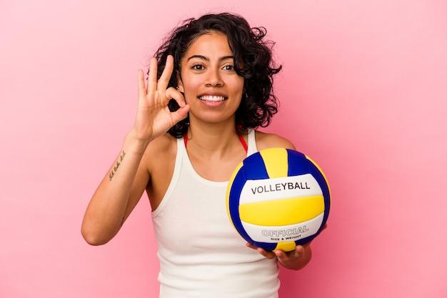 Młoda latynoska kobieta trzymająca piłkę do siatkówki na różowym tle wesoła i pewna siebie