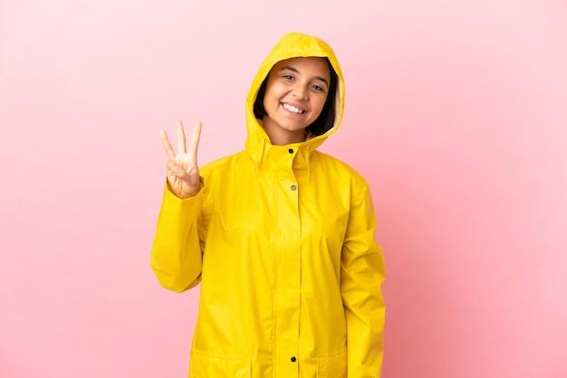 Młoda latynoska kobieta ubrana w płaszcz przeciwdeszczowy na odosobnionym tle szczęśliwa i licząca trzy palcami