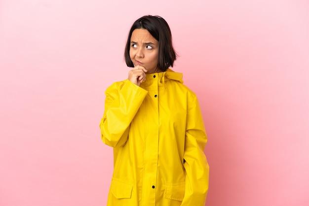 Młoda latynoska kobieta ubrana w przeciwdeszczowy płaszcz na białym tle, mająca wątpliwości i zdezorientowany wyraz twarzy