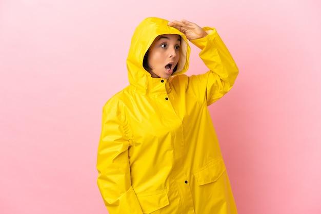 Młoda latynoska kobieta ubrana w przeciwdeszczowy płaszcz na białym tle z wyrazem zaskoczenia, patrząc z boku
