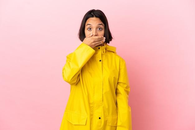Młoda latynoska kobieta ubrana w przeciwdeszczowy płaszcz na białym tle, zakrywająca usta dłonią