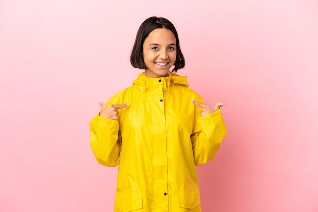 Młoda latynoska kobieta ubrana w przeciwdeszczowy płaszcz na odosobnionym tle dumna i zadowolona z siebie