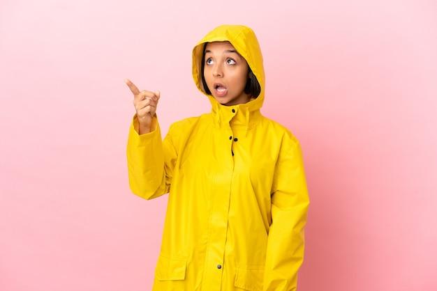 Młoda latynoska kobieta ubrana w przeciwdeszczowy płaszcz na odosobnionym tle i wskazująca daleko