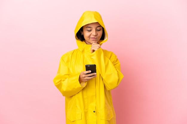 Młoda latynoska kobieta ubrana w przeciwdeszczowy płaszcz na odosobnionym tle, myśląca i wysyłająca wiadomość