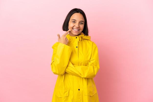 Młoda latynoska kobieta ubrana w przeciwdeszczowy płaszcz na odosobnionym tle, pokazująca gest kciuka w górę