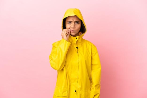 Młoda latynoska kobieta ubrana w przeciwdeszczowy płaszcz na odosobnionym tle pokazująca znak gestu ciszy