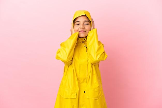 Młoda latynoska kobieta ubrana w przeciwdeszczowy płaszcz na odosobnionym tle sfrustrowana i zakrywająca uszy