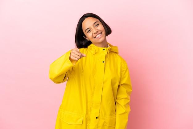 Młoda latynoska kobieta ubrana w przeciwdeszczowy płaszcz na odosobnionym tle wskazujący przód z radosnym wyrazem twarzy