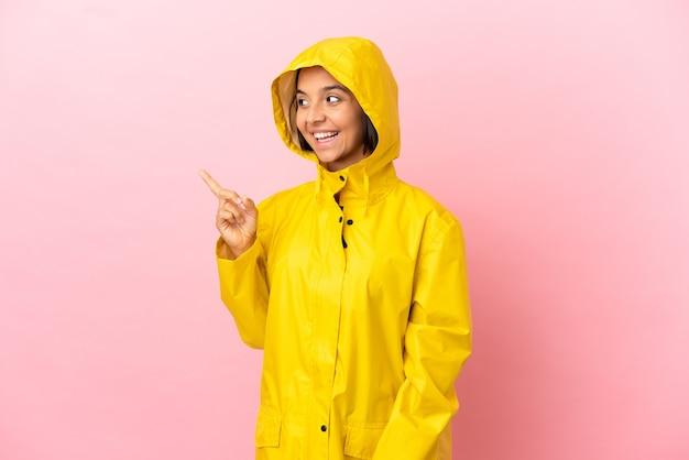 Młoda latynoska kobieta ubrana w przeciwdeszczowy płaszcz na odosobnionym tle, zamierzająca zrealizować rozwiązanie, podnosząc palec w górę