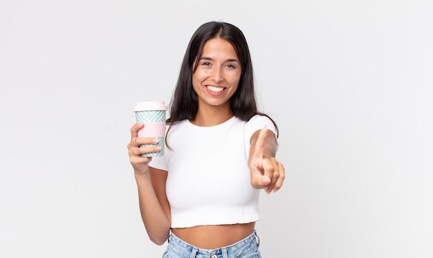 Młoda latynoska kobieta uśmiecha się dumnie i pewnie robi numer jeden i trzyma pojemnik na kawę na wynos