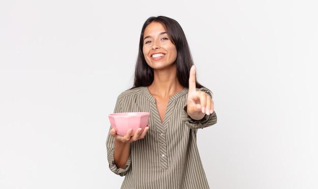 Młoda latynoska kobieta uśmiecha się dumnie i pewnie robi numer jeden i trzyma pustą miskę lub garnek