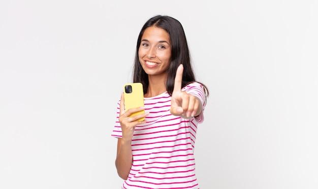 Młoda latynoska kobieta uśmiecha się dumnie i pewnie robi numer jeden i trzyma smartfona